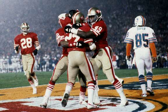 Teammats mob San Francisco 49ers safety Carlton Williamson (27) after Williamson intercepts a pass during Super Bowl XIX, a 38-16 victory over the Miami Dolphins on January 20, 1985, at Stanford Stadium in Stanford, California. (Photo by Rob Brown/Getty Images) *** Local Caption ***