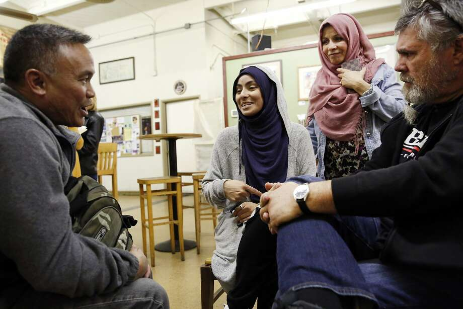 "Bert Palmon, left, has a discussion with group organizer Jehan Hakim, her mother Shukrin Hakim, and attendee Manny Botelho, following a ""Meet a Muslim Community Conversation"", a public gathering designed to build bridges with the Muslim community, held at the Mission Coffee Roasting Company in Fremont, CA Monday, February 1, 2016. Photo: Michael Short, Special To The Chronicle"