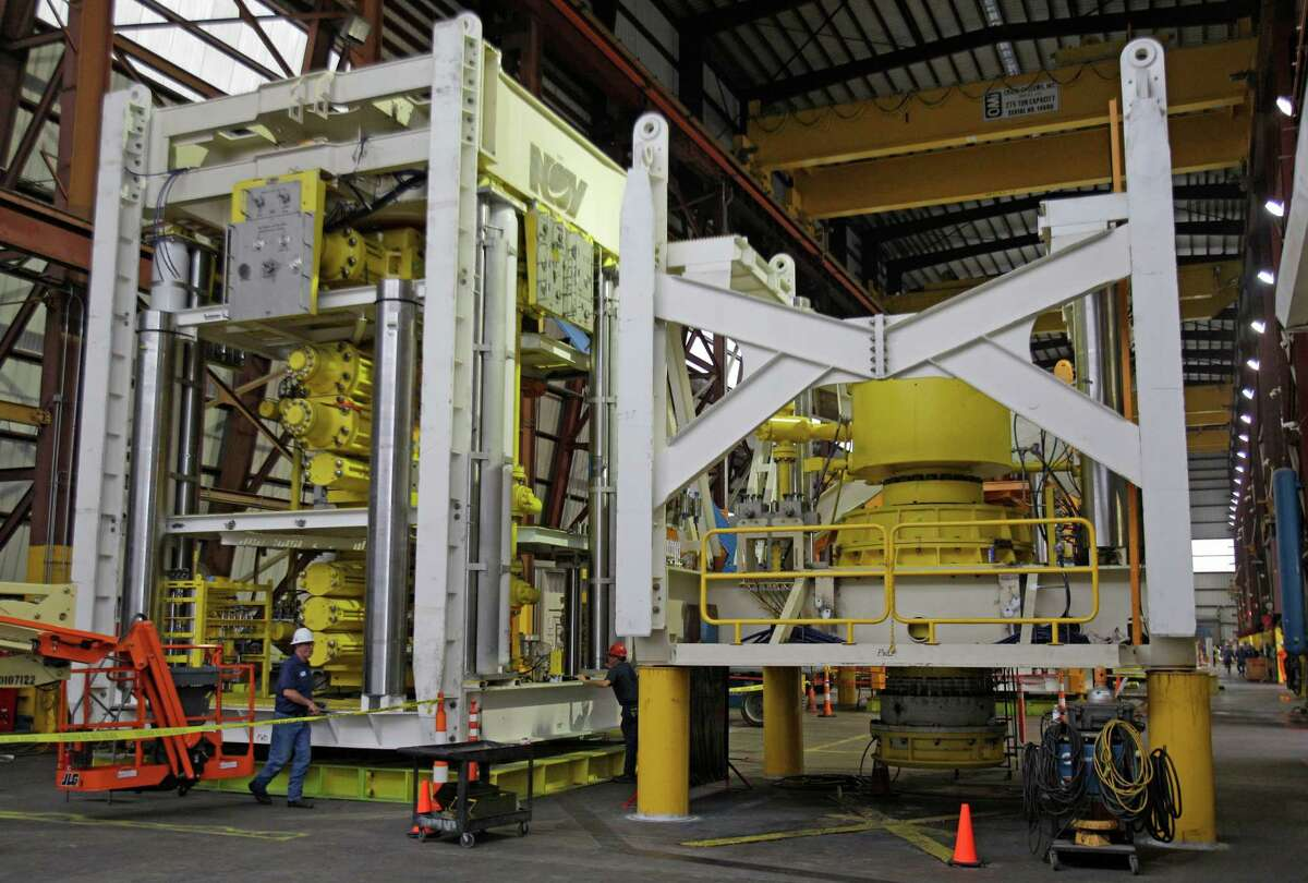 Employees at National Oilwell Varco, 6390 N. Eldridge Parkway, work on a lower blowout preventer stack, shown left, and lower marine riser package, shown right, Thursday, April 18, 2013, in Houston. ( Melissa Phillip / Houston Chronicle )