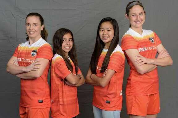Dash defender Allysha Chapman, left, and forward Janine Beckie, right, model the team's new uniform and are joined by aspiring youth soccer players Dannielle Shannon, second from left, and Lori Do.