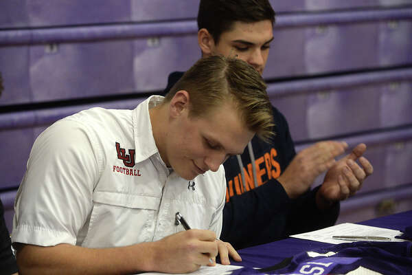 Port Neches-Groves High School's Adam Morse re-enacts the signing of his letter of intent to play football for Lamar University during Wednesday's national signing day ceremony. Players gathered with coaches, students, staff, family and friends in the gymnasium for the event, at which they joined the scores of high school athletes across the country officially committing to their college offers. Refreshments were enjoyed following the signing and group photos.  Photo taken Wednesday, February 3, 2016  Kim Brent/The Enterprise
