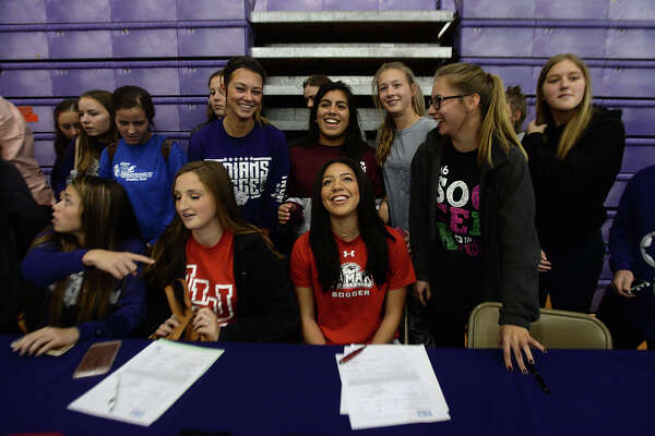 Port Neches-Groves High School's Mikayla Johnson (center) is swarmed by soccer teammates as they gather for a photo with the future Lamar player during Wednesday's national signing day ceremony. Players gathered with coaches, students, staff, family and friends in the gymnasium for the event, at which they joined the scores of high school athletes across the country officially committing to their college offers. Refreshments were enjoyed following the signing and group photos. Photo taken Wednesday, February 3, 2016 Kim Brent/The Enterprise