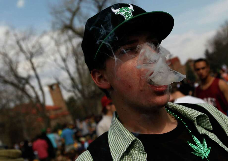 "BOULDER, CO - APRIL 20:  A student smokes a marijuana cigarette during a ""smoke out"" with thousands of others April 20, 2010 at the University of Colorado in Boulder, Colorado.   April 20th has become a de facto holiday for marijuana advocates, with large gatherings and ""smoke outs"" in many parts of the United States.  Colorado, one of 14 states to allow use of medical marijuana, has experienced an explosion in marijuana dispensaries, trade shows and related businesses in the last year as marijuana use becomes more mainstream here. Photo: Chris Hondros, Getty Images / 2010 Getty Images"