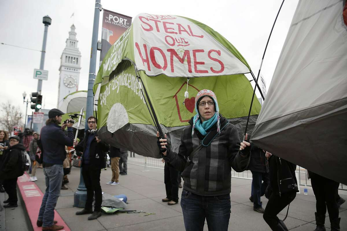 Protesters hold tents off the ground to avoid arrest during a protest on homelessness along the Embarcadero on Wednesday, February 3, 2016 in San Francisco.