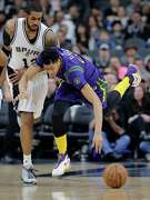 New Orleans Pelicans forward Anthony Davis (23) is tripped up after he was fouled by San Antonio Spurs forward LaMarcus Aldridge (12) during the first half of an NBA basketball game Wednesday, Feb. 3, 2016, in San Antonio. (AP Photo/Eric Gay)