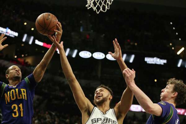 Spurs' Kyle Anderson goes for a rebound against New Orleans Pelicans' Bryce Dejean-Jones (31) and Omer Asik during the first half at the AT&T Center on Feb. 3, 2016.