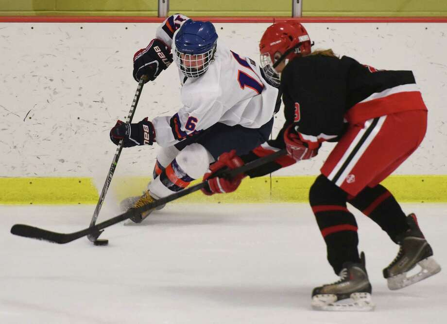 Stamford-Westhill-Staples' Kyra DalBello, left, moves around New Canaan defender Emma Patch in Stamford-Westhill-Staples' 7-3 win over New Canaan in the high school girls hockey game at Terry Conners Rink in Stamford, Conn. Wednesday, Jan. 14, 2015. Photo: Tyler Sizemore / Tyler Sizemore / Greenwich Time