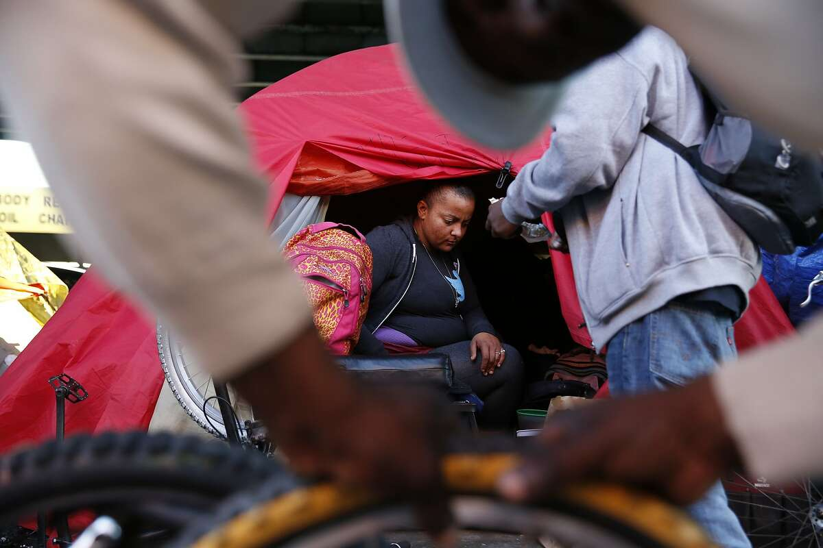 Ana Held (center), who is homeless, looks out the entrance of her tent along 13th Street at the activity outside on Wednesday, January 27, 2016 in San Francisco, Calif.