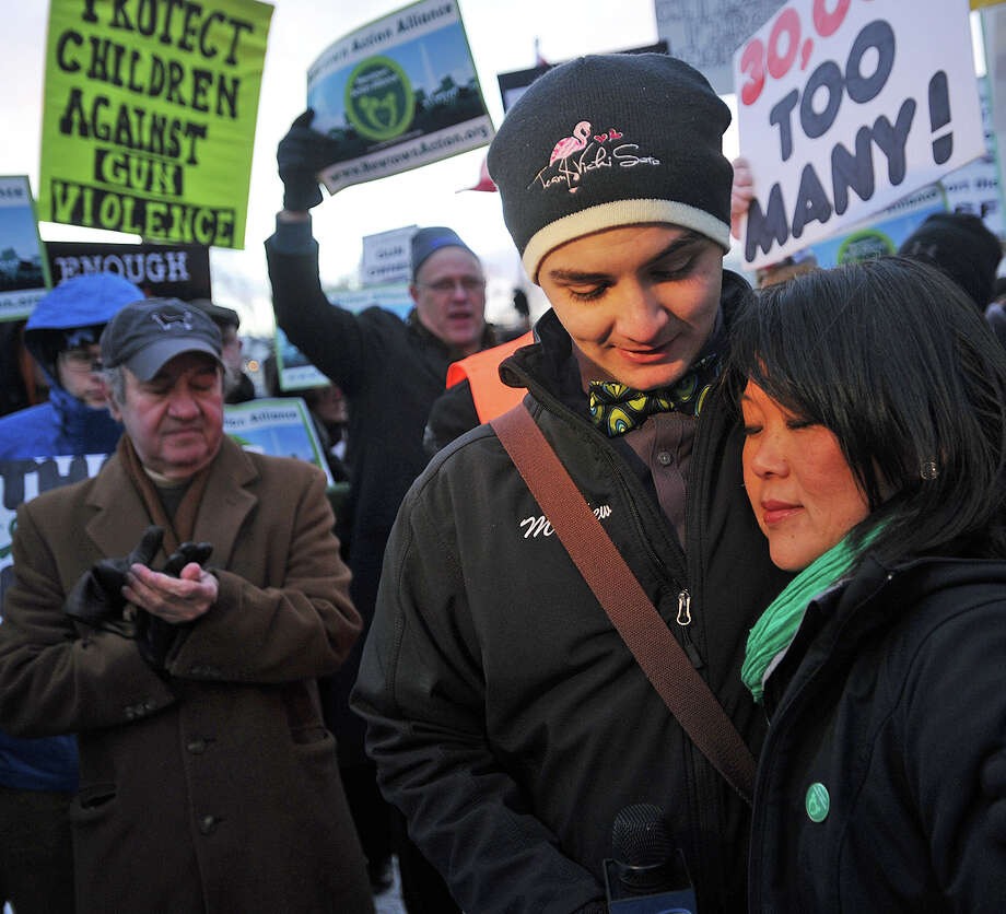 Matthew Soto, the brother of Sandy Hook massacre victim Victoria Soto, hugs Po Murray, chairwoman of Newtown Action Alliance, during a rally outside the National Shooting Sports Foundation's corporate headquarters in Newtown. Photo: Brian A. Pounds / Hearst Connecticut Media / Connecticut Post