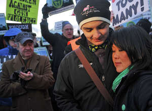 Matthew Soto, the brother of Sandy Hook massacre victim Victoria Soto, hugs Po Murray, chairwoman of Newtown Action Alliance, during a rally outside the National Shooting Sports Foundation's corporate headquarters in Newtown.