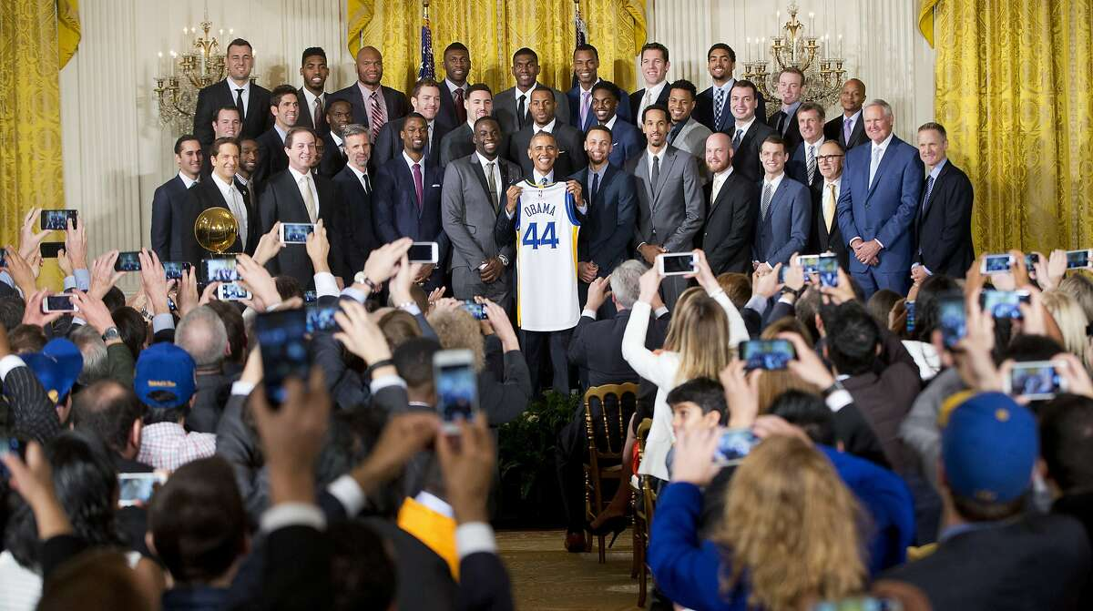 President Barack Obama holds up Golden State Warrior basketball jersey given to him by team members during a ceremony in the East Room of the White House in Washington, Thursday, Feb. 4, 2016, where he honored the 2015 NBA Champions.