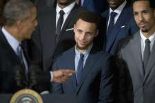 President Barack Obama points to Golden State Warrior basketball player Stephen Curry, center,  during a ceremony in the East Room of the White House in Washington, Thursday, Feb. 4, 2016, where the president honored the 2015 NBA Champions. At right is Warriors guard Shaun Livingston. (AP Photo/Pablo Martinez Monsivais)