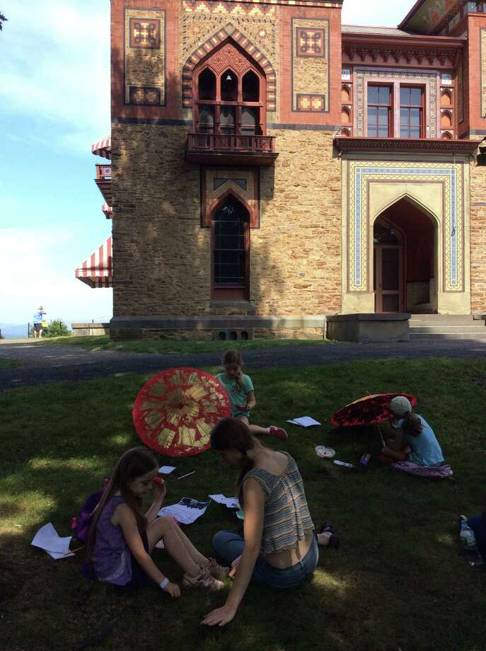 Students relax on the grass during a field trip to Olana in Hudson. (The Olana Partnership)