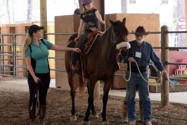 Instructor Cassie McCollum shows Janelle King exercises to perform as Janelle rides Sayed, led by John Faltow, at Inspiration Ranch, 25826 Glen Loch Drive, in Spring.