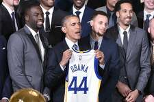 US President Barack Obama holds a jersey while poseing with  forward Draymond Green (L), Golden State Warriors guard Stephen Curry (2nd R) and guard Shaun Livingston (R) during an event honoring the 2015 NBA Champion Golden State Warriors in the East Room of the White House on February 4, 2015 in Washington, DC. / AFP / MANDEL NGANMANDEL NGAN/AFP/Getty Images