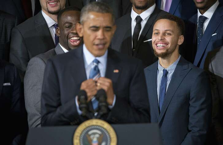 Warriors players, Draymond Green, left, and Stephen Curry, right, react to watching President Barack Obama mimicking Curry's 'clowning,' during a ceremony honoring the 2015 NBA champions Thursday at the White House.