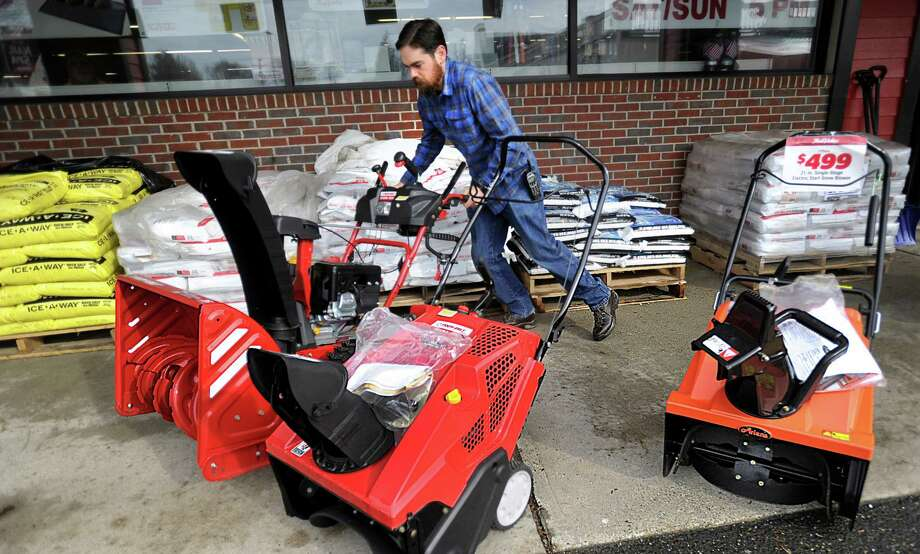 Ryan Clifford, an owner of True Value Hardware in Bethel, moves snowblowers into their display spot outside after the Dolan Plaza store Thursday, February 4, 2016. He moved them out of the rain earlier. True Value has a full supply of shovels, salt and sand due to a mild winter, Thursday, Feb. 4, 2016. Photo: Carol Kaliff / Hearst Connecticut Media / The News-Times
