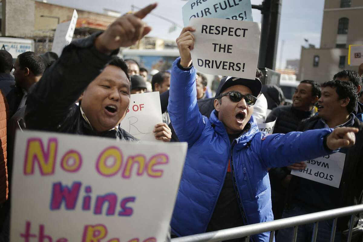 Uber drivers, including Kalsang Tsering, right, chant and yell as people enter and leave an Uber office in New York, Monday, Feb. 1, 2016. Some Uber drivers in New York City say they are going on strike to protest the company's decision to cut fares in the city by 15 percent. (AP Photo/Seth Wenig)