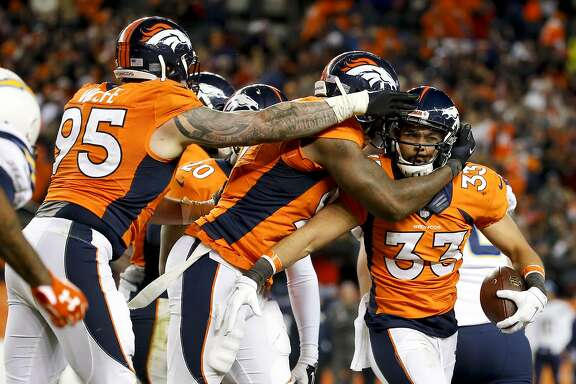 FILE- In this Jan. 3, 2016, file photo, Denver Broncos defensive back Shiloh Keo, right, celebrates after an interception with Derek Wolfe, left, and Malik Jackson during the second half in an NFL football game against the San Diego Chargers in Denver. By most accounts, this year's Broncos do, in fact, go out kicking and screaming on most weeks, showing a fire that was strangely lacking under the teams coached by John Fox, especially in their final games of each of his four seasons. (AP Photo/Jack Dempsey, File0