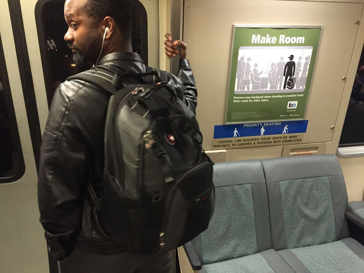 Faced with overcrowded trains, BART launched a public service message campaign to encourage riders to take their backpacks off to make more room for those standing on cars. This train was nearing the end of the Richmond line, when the car had emptied out enough to get a clear photograph of BART's new poster. Backpacks are encouraged to be held lower when there is standing room only, but obviously not an issue when there are plenty of empty seats as shown in this shot. This passenger had his backpack off earlier in the train ride before donning it to exit the car. Photo from February 3rd, 2016.