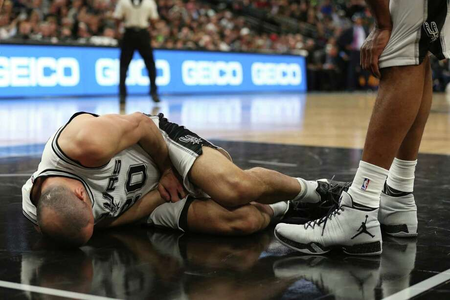 Spurs' Manu Ginobili lies on the court after he was kneed by the New Orleans Pelicans' Ryan Anderson during the second half at the AT&T Center, on Feb. 3, 2016. Anderson was called for an offensive foul. Photo: JERRY LARA, Staff / San Antonio Express-News / © 2016 San Antonio Express-News
