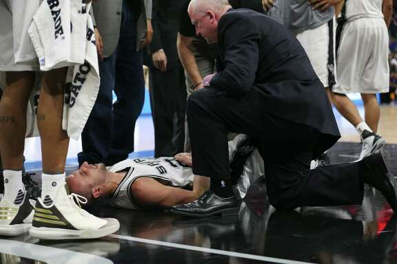 San Antonio Spurs' head athletic trainer Will Sevening checks on Manu Ginobili after he was kneed by New Orleans Pelicans' Ryan Anderson late in the fourth quarter at the AT&T Center, Wednesday, Feb. 3, 2016.