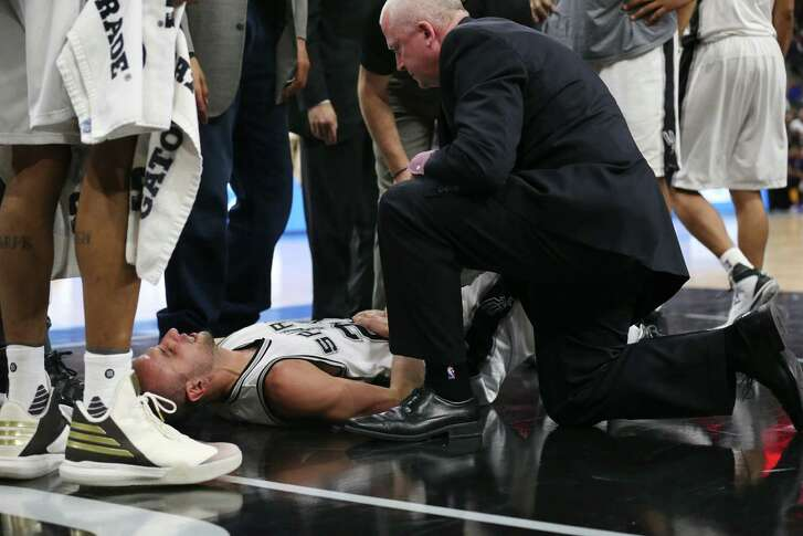 Spurs head athletic trainer Will Sevening checks on Manu Ginobili after he was kneed by New Orleans Pelicans' Ryan Anderson late in the fourth quarter at the AT&T Center on Feb. 3, 2016.