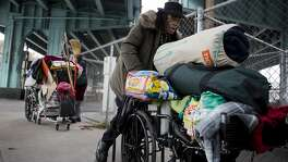 Timothy Blevins pushes a wheelchair full of his belongings to a new location after police and city workers swept the area where he was staying under the I-80 underpass near 8th and Bryant Street on Tuesday, January 26, 2016 in San Francisco, Calif.