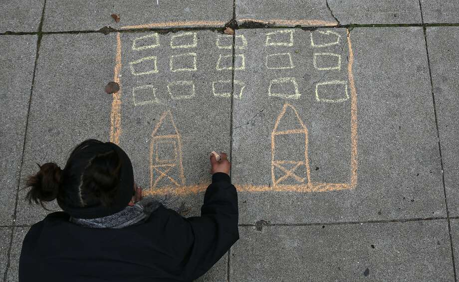 Teresa Sandoval draws a house in chalk on the sidewalk along Trainor Street across from the biggest street encampment in the city during a news conference held by Poor Magazine to call more attention to the plight of the homeless. Photo: Lea Suzuki, The Chronicle