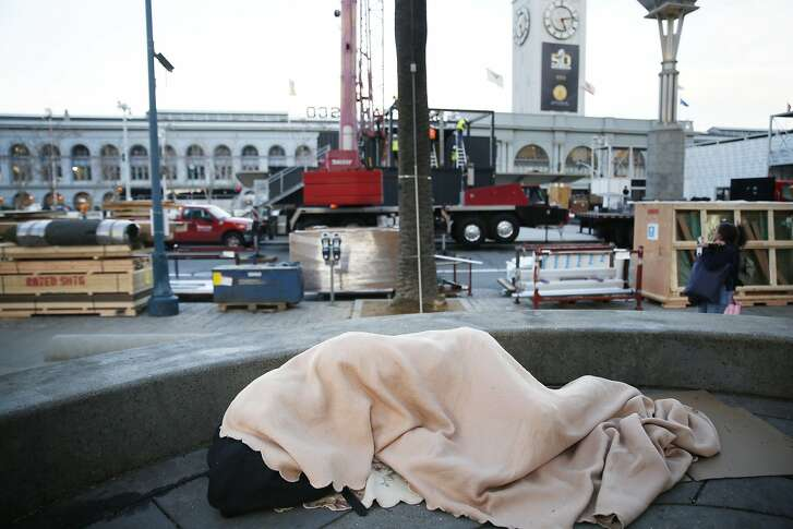 Selassie Sereño, sleeps on the ground under a blanket along the Embarcadero as the Super Bowl City begins to be built around her on Monday, January 25, 2016 in San Francisco, Calif.