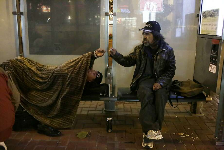 Hector Arturo (l to r) hands Jose a cigarette as they share it while keeping dry out of the rain at a bus stop on Market and Steuart Streets in the early hours of Wednesday, January 13, 2016 in San Francisco, Calif. Photo: Lea Suzuki, The Chronicle