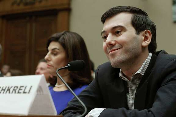 Martin Shkreli, former CEO of Turing Pharmaceuticals, smiles while flanked by Nancy Retzlaff, chief commercial officer for Turing, during a House Oversight and Government Reform Committee hearing Thursday on Capitol Hill.