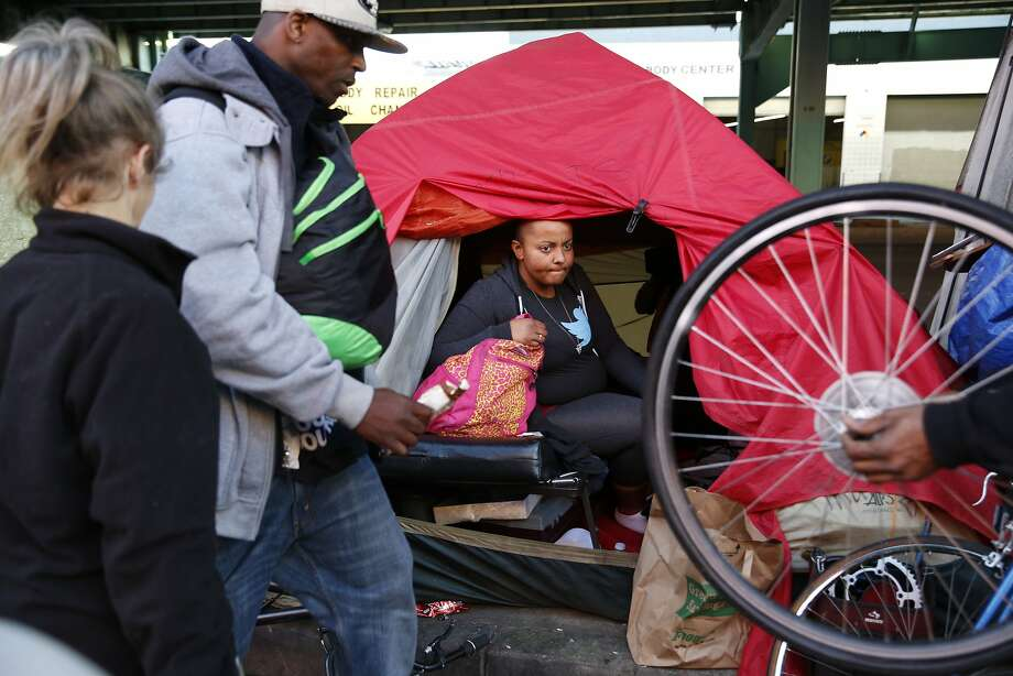 Ana Held (center), who is homeless, looks out the entrance of her tent along 13th Street at the activity outside on Wednesday, January 27, 2016 in San Francisco, Calif. Photo: Lea Suzuki, The Chronicle