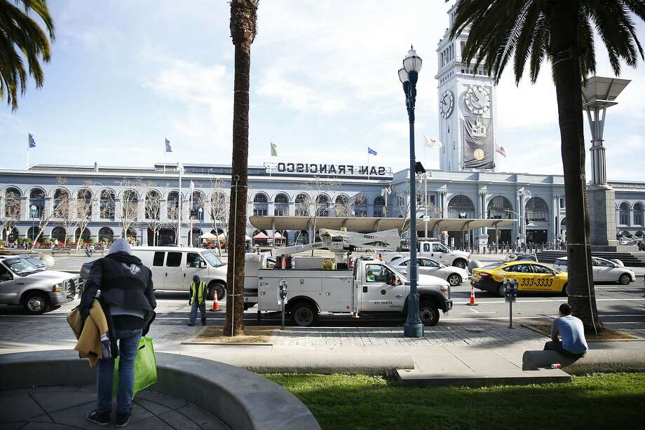 Selassie Sereño, who is homeless, lays her belongings on the ground along the Embarcadero. Photo: Lea Suzuki, The Chronicle