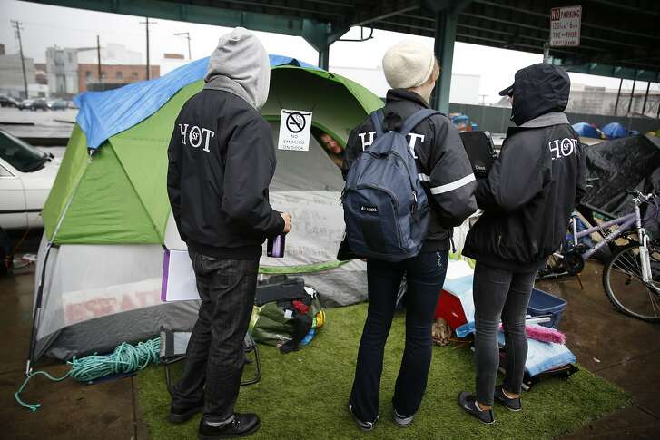 Brenda Meskan (l to r),  San Francisco Homeless Outreach Team director, (front left to right), Rebecca Pfeifer-Rosenblum, San Francisco Homeless Outreach Team  staff,  and Joanna Gobea, San Francisco Homeless Outreach Team  staff,  talk to Oscar (back face in tent opening) as he peeks out of his tent along 13th Street on Friday, January 22, 2016 in San Francisco, Calif.