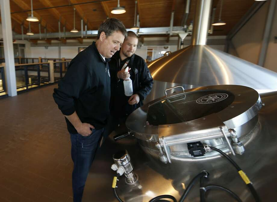 Todd Usry (front), president of Breckenridge Brewery, checks beer brewing in the company's factory. The Littleton, Colo., firm was bought by AB InBev. Photo: David Zalubowski, Associated Press