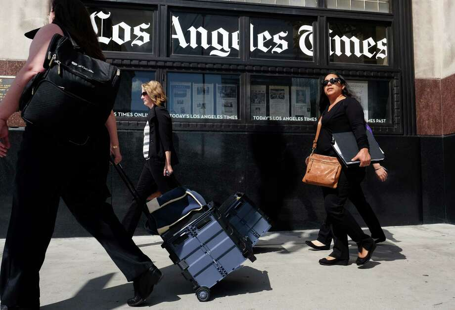 FILE - In this Monday, Oct. 5, 2015, file photo, pedestrians walk past the Los Angeles Times building in downtown Los Angeles. Tribune Publishing announced Thursday, Feb. 4, 2016, that the company is getting a $44.4 million cash boost from investor Michael W. Ferro Jr., chairman and CEO of Chicago's Merrick Media, who will become the nonexecutive chairman of the company that owns the Chicago Tribune and the Los Angeles Times. (AP Photo/Richard Vogel, File) ORG XMIT: NYBZ463 Photo: Richard Vogel / AP