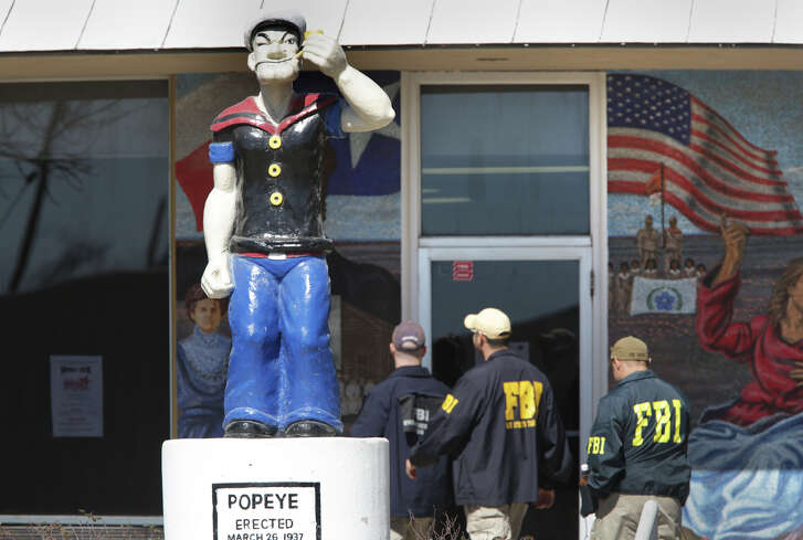 FBI agents walk into Crlystal City City Hall past a statue of Popeye, the city's mascot, siezing computers and documents and arresting 5 or 6 including city council members and the mayor, on Thursday, Feb. 4, 2016.