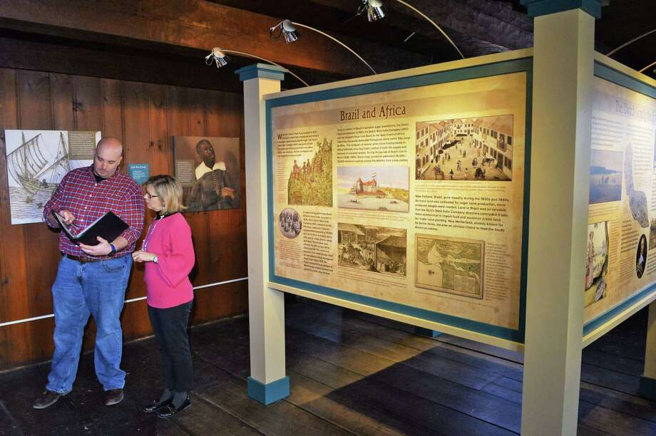 "Historic site assistant Geoff Benton, left, and site manager Heidi Hill ready the new exhibit ""A Dishonorable Trade: Human Trafficking in the Dutch Atlantic World,"" about the Van Rensselaer family's slaves at the Fort Crailo state historic site Thursday Jan. 28, 2016 in Rensselaer, NY.  (John Carl D'Annibale / Times Union) Photo: John Carl D'Annibale / 10035179A"