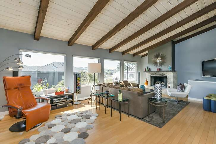 A quartet of picture windows welcomes natural light into a living room topped by a vaulted, beamed ceiling.