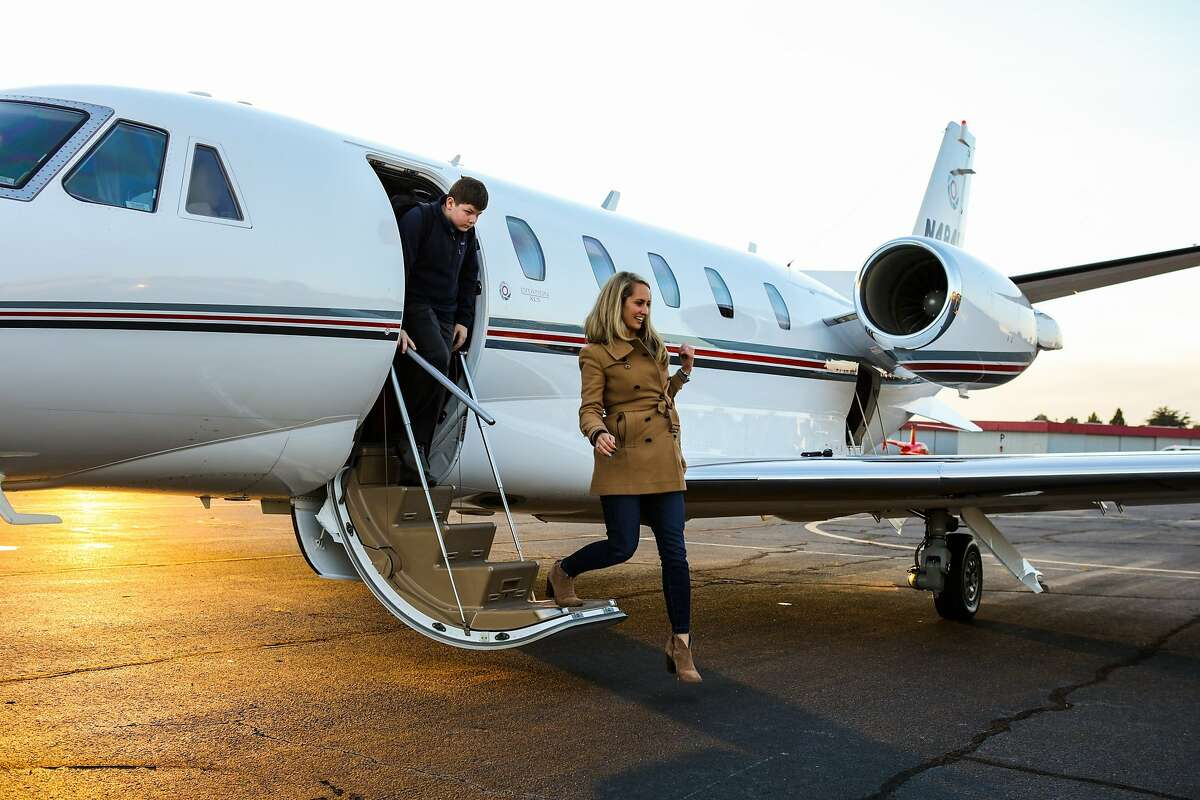 Micah Herndon and Kelly Snider, who are visiting from Charlotte, North Carolina, disembark from a private plane at the APP jet center in Hayward, California on Thursday, February 4, 2016. They are in town for the Super Bowl and are rooting for the Denver Broncos.