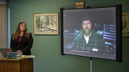 Attorney Lissa Casey listens to a recorded statement by Ammon Bundy as an image of him is shown on a screen, in Eugene, Ore. Bundy as 15 others have been indicted in connection with the monthlong standoff at Malheur National Wildlife Refuge.