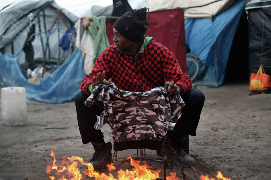 A migrant dries his clothes above a fire, in the migrant camp of Calais, north of France, Thursday, Feb. 4, 2016. About 4,000 people from Syria, Sudan and other countries are estimated to be camped out in Calais as they try to reach Britain, some recently moving into new facilities but most still sleeping in what's been called Europe's biggest slum. (AP Photo/Thibault Camus) ORG XMIT: XTC105 Photo: Thibault Camus / AP