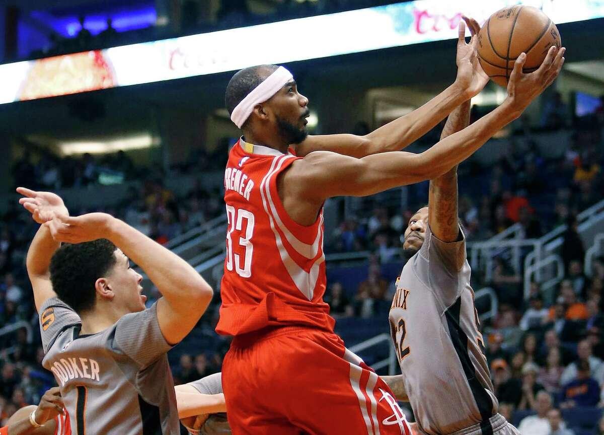 Houston Rockets guard Corey Brewer (33) drives between Phoenix Suns guards Devin Booker (1) and Jordan McRae during the first quarter of an NBA basketball game Thursday, Feb. 4, 2016, in Phoenix. (AP Photo/Rick Scuteri)