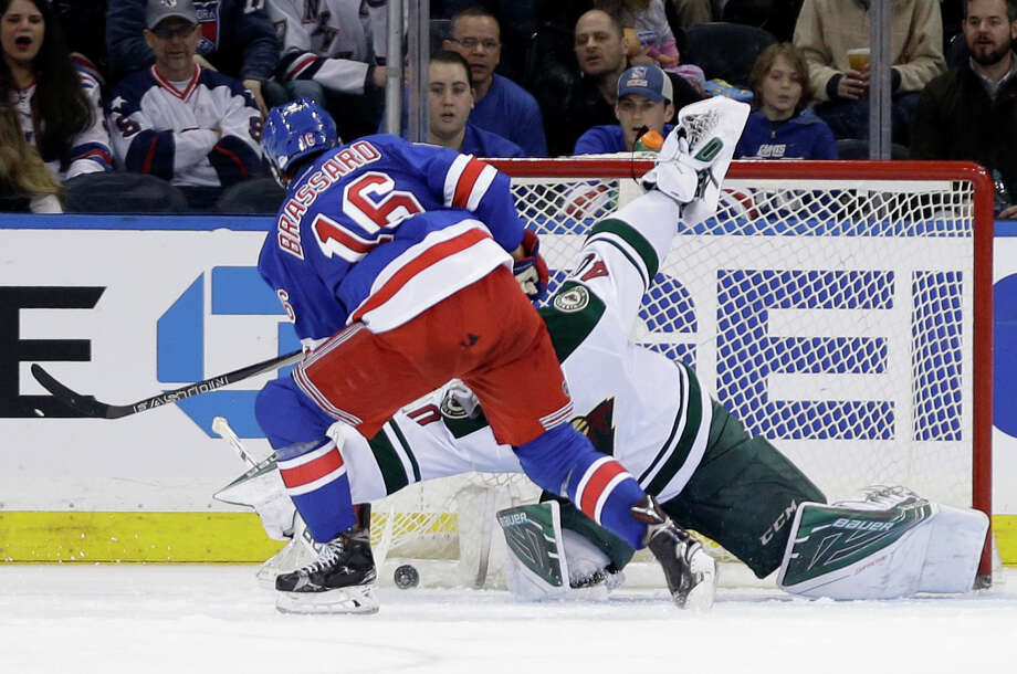 New York Rangers center Derick Brassard (16), left, scores the go-ahead goal past Minnesota Wild goalie Devan Dubnyk (40) during the third period of the NHL hockey game, Thursday, Feb. 4, 2016, in New York. The Rangers defeated the Wild 4-2. (AP Photo/Seth Wenig) ORG XMIT: NYSW107 Photo: Seth Wenig / AP
