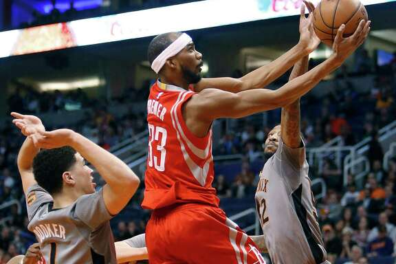 On his way to a 24-point game, Corey Brewer drives between the Suns' Devin Booker, left, and Jordan McRae.