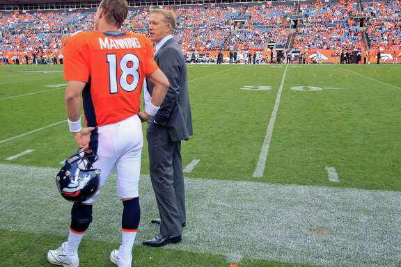 Denver Broncos executive vice president of football operations John Elway, right, talks with quarterback Peyton Manning  during the fourth quarter of an NFL football game against the Oakland Raiders in Denver.