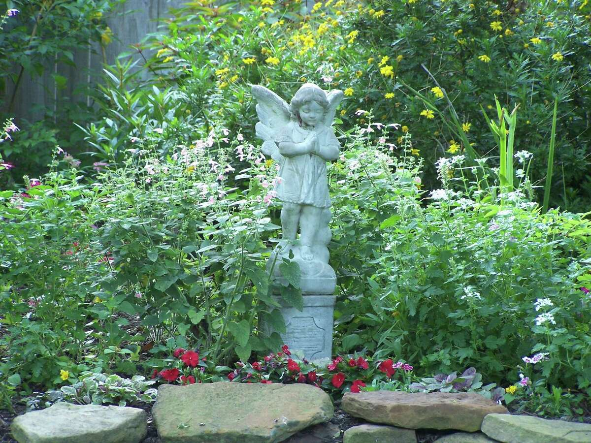 An angel statue watches over the backyard of Amy Backlas in Houston near the energy corridor. Her yard is is wildlife certified and draws lots of birds, bees, butterflies and other pollinators.