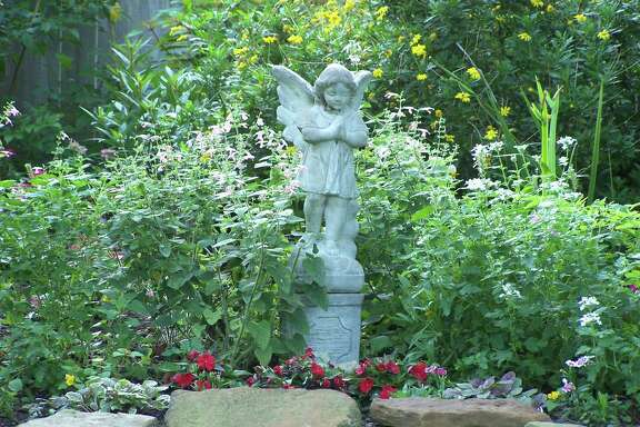 An angel statue watches over the backyard of Amy Backlas in Lake Jackson. Her yard is is wildlife certified and draws lots of birds, bees, butterflies and other pollinators.