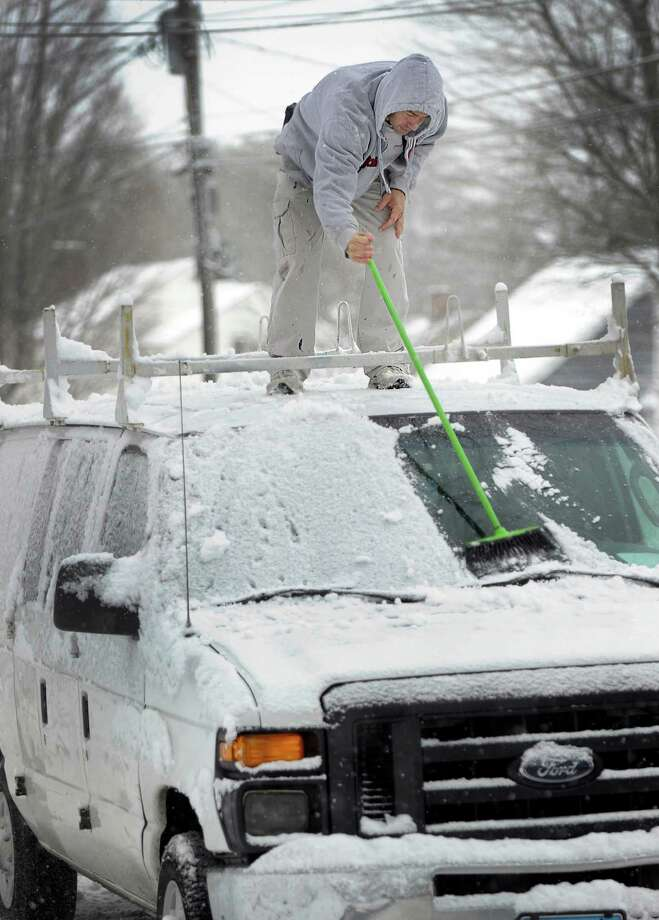 Eliandro Souza, climbs on the roof of his van to clean off the snow so he can get to his job as a painter on West Wooster Street in Danbury, Friday, Feb. 5, 2016. Photo: Carol Kaliff, Hearst Connecticut Media / The News-Times